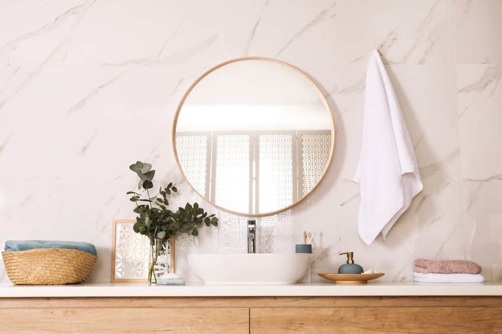 Wooden vanity with vessel sink and a round mirror fixed against the white marble wall.