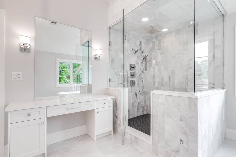 Bathroom with a walk-in shower and a white vanity paired with a frameless mirror.