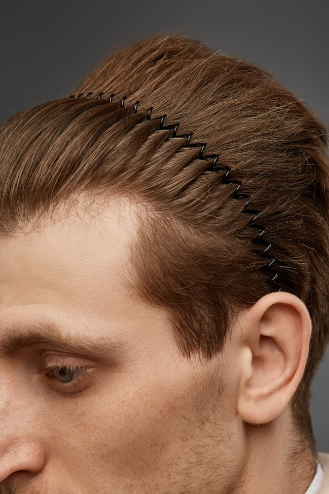 A close look at a man wearing a thin black wavy headband.