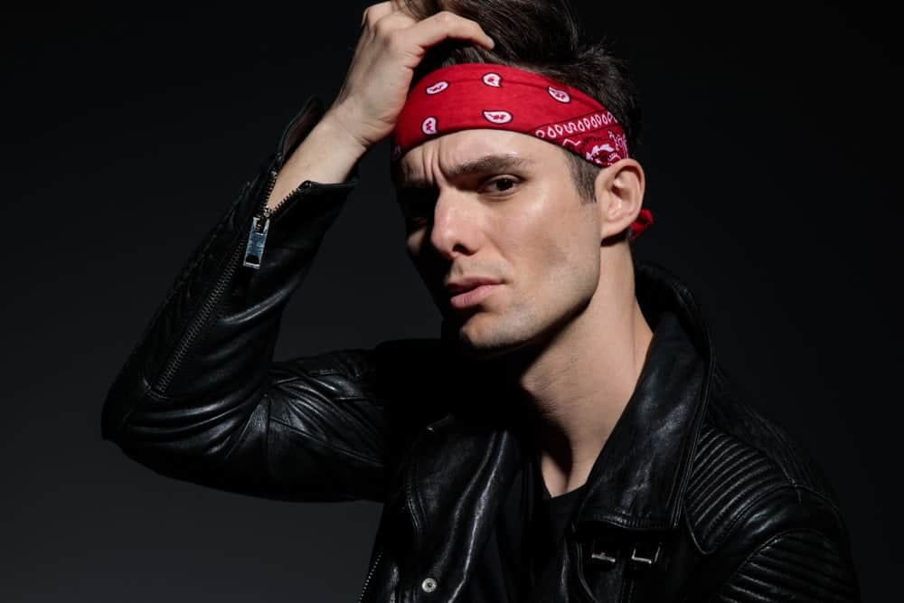 A man wearing a black leather jacket and a bandana headband.