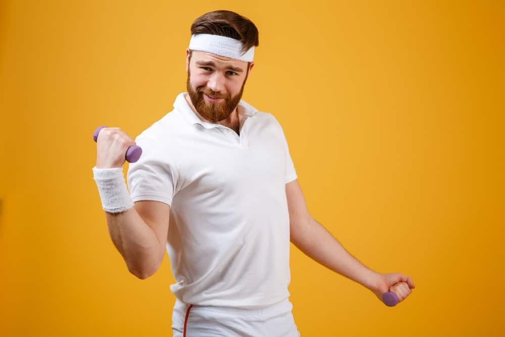 A man wearing a white headband while exercising.