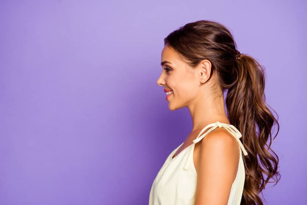 A side-view of a woman with her brunette hair up in a ponytail.