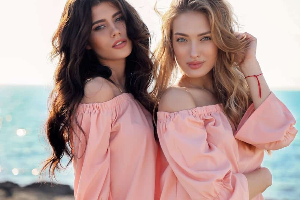 Two woman in pink dresses and wavy hair.