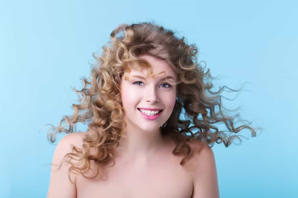 Woman with long curly hairstyle against a pale blue background.