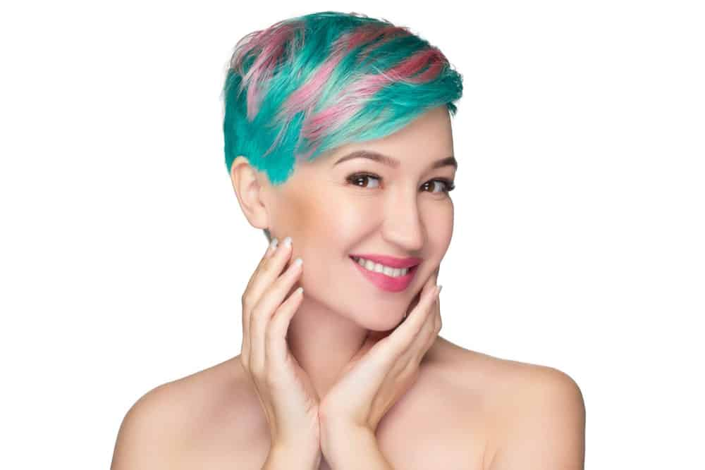 Beautiful woman with short dyed hair smiles and touches her face.