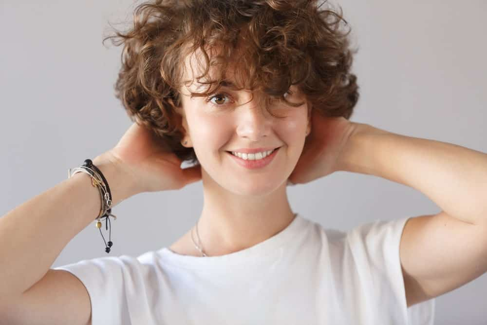 Woman with short curly hair and bangs holding the back of her head.