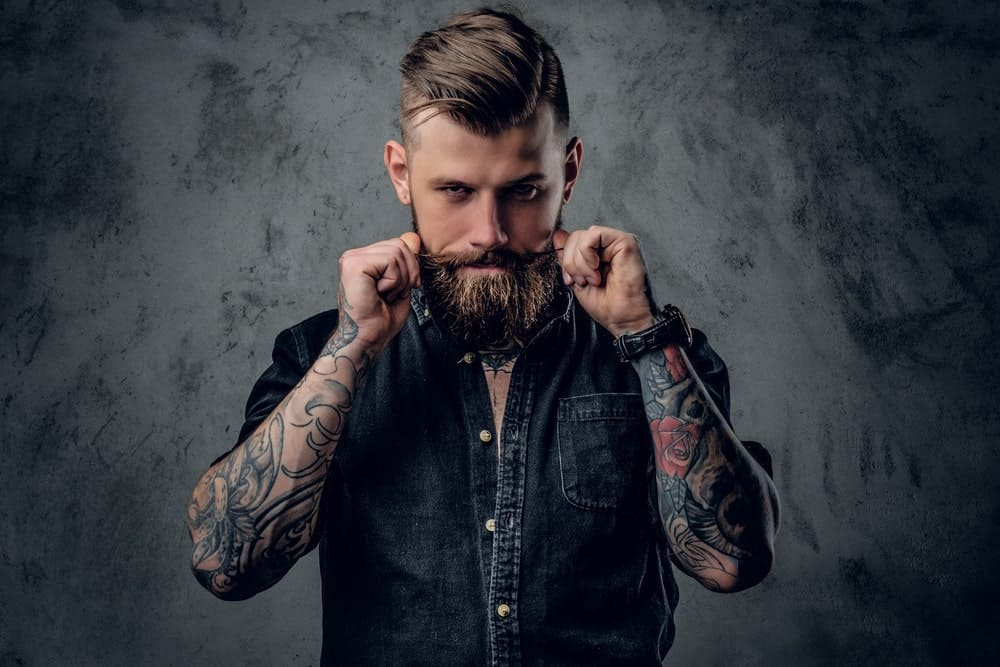 Man with sleeve tattoos styling his beard.