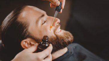 A barber applying oil on a man's beard through a dropper.
