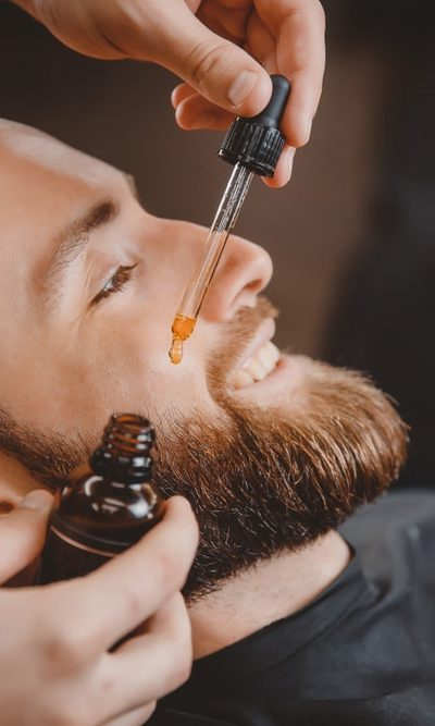 A barber applying oil on a man's beard through a dropper.