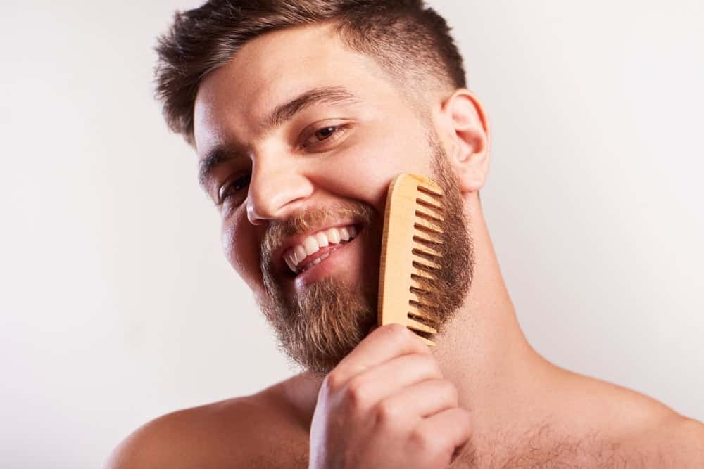A man combing his beard.