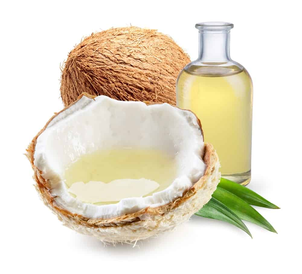 A bottle of coconut oil along with fresh nuts.