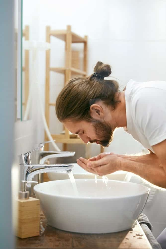 Man with full beard washing his face on the bathroom sink.