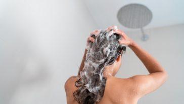 A woman shampooing her long brunette hair.