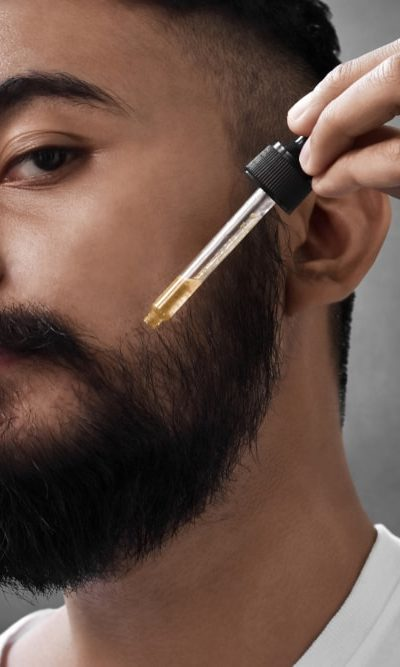 A bearded man applying coconut oil to his beard.