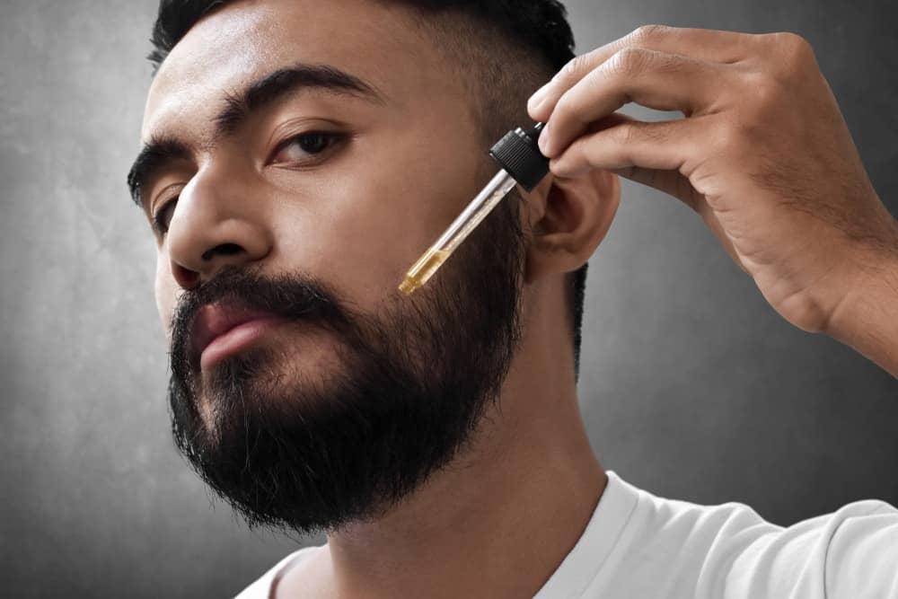 A bearded man applying coconut oil to his beard.