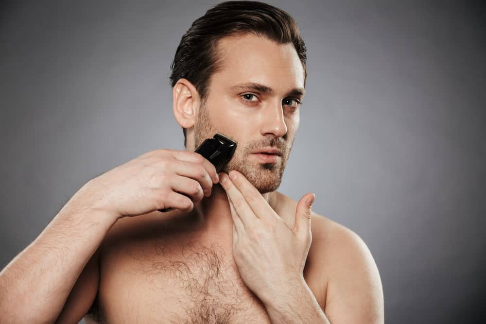 A man shaving his beard using an electric razor.