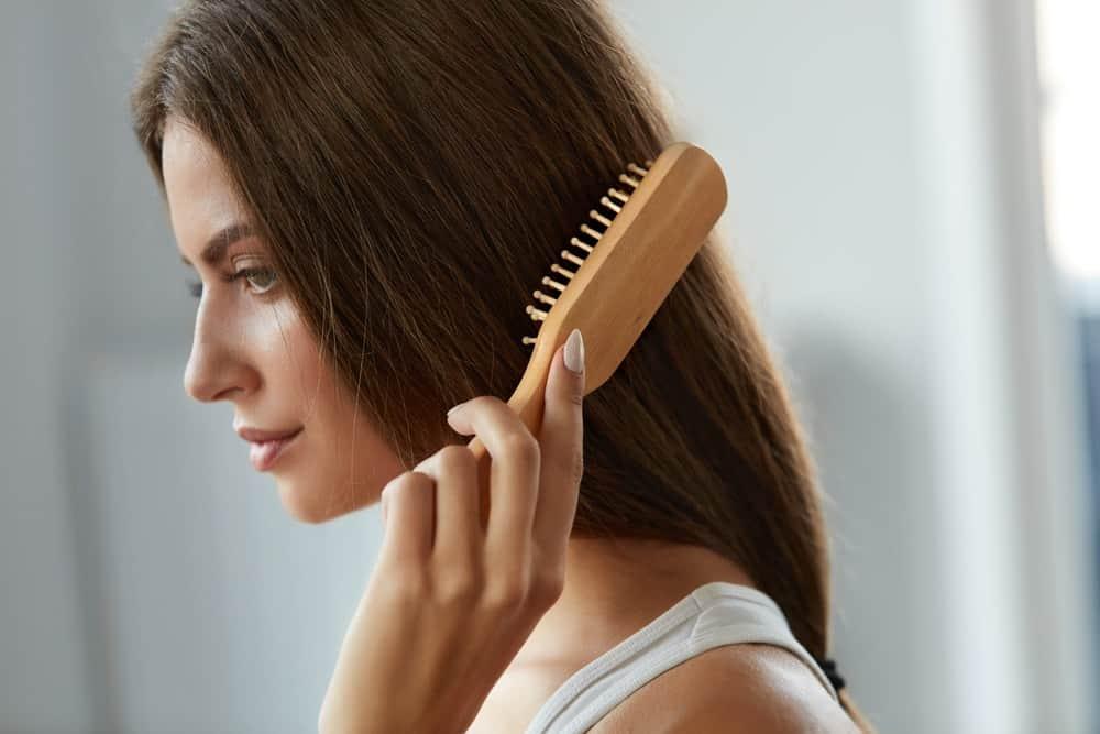 A woman brushing her long brown hair.