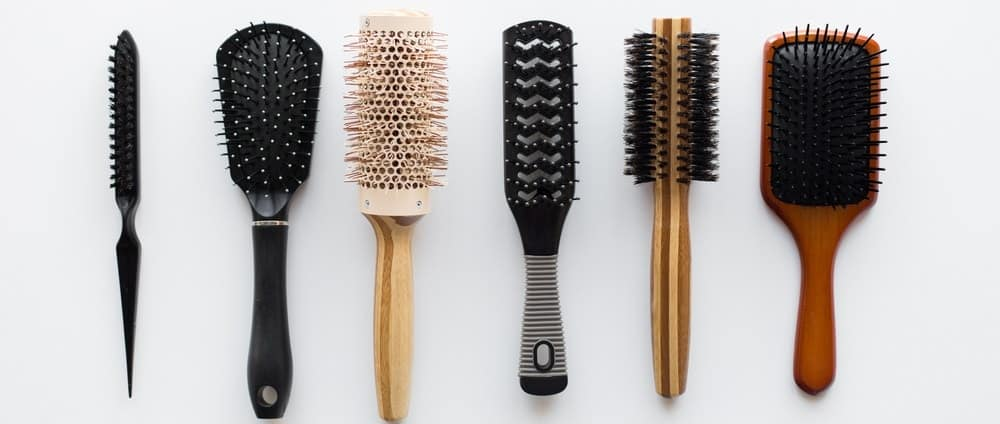 A row of hair brushes on a white surface.