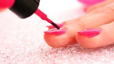 A close look at a woman putting on pink nail polish.