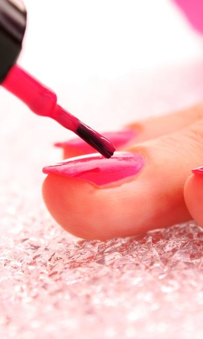A close look at a woman putting on pink nail polish.