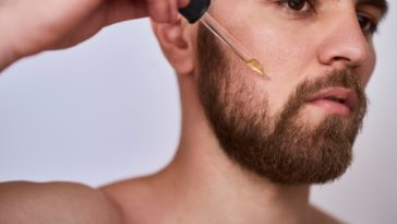 A bearded man putting beard oil on his beard.