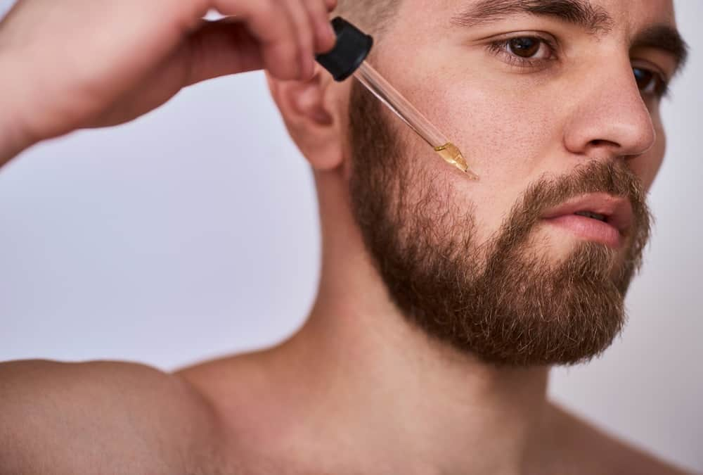 A bearded man putting beard oil on his beard.