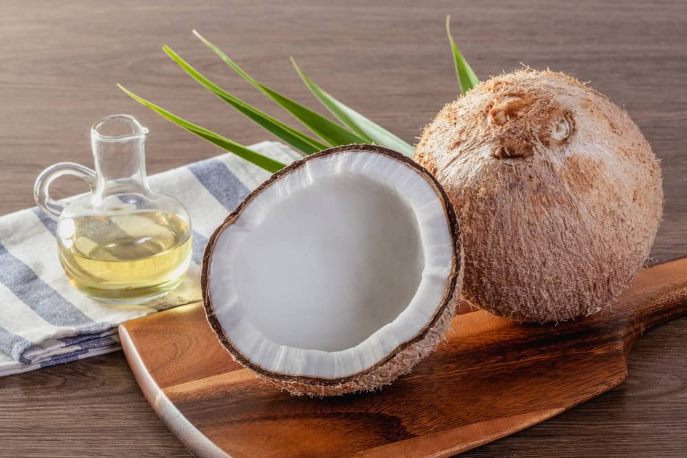 A glass bottle of coconut oil next to raw coconuts.
