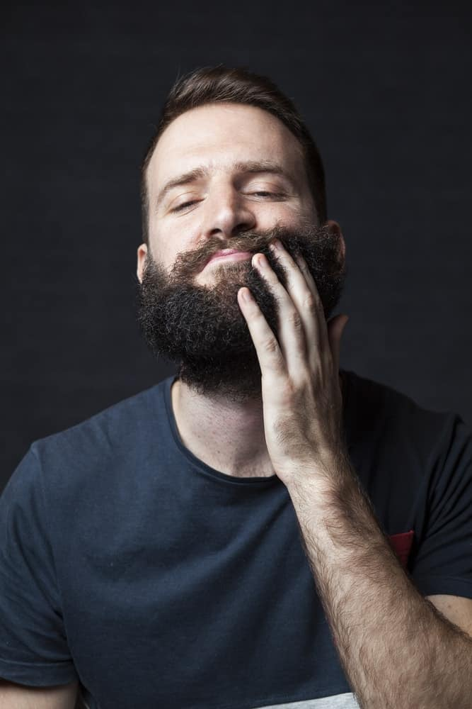 A bearded man applying beard oil on his thick beard.