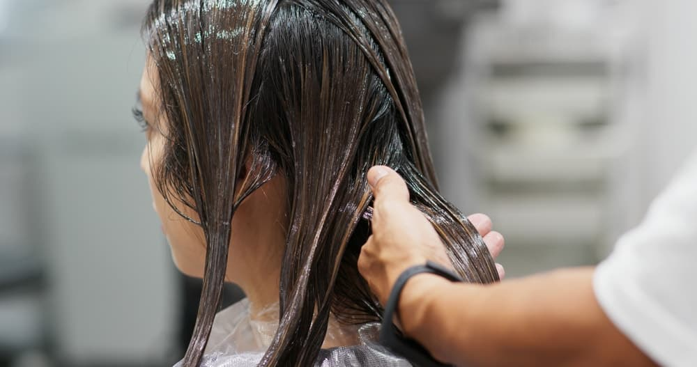 A woman having her hair treated and straightened at the salon.