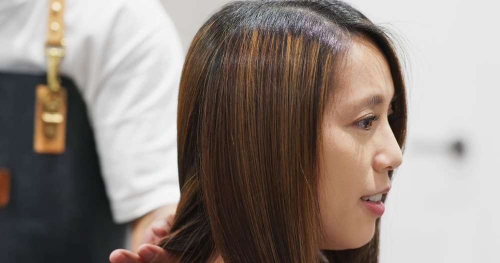 A woman having her hair straightened at the parlor.