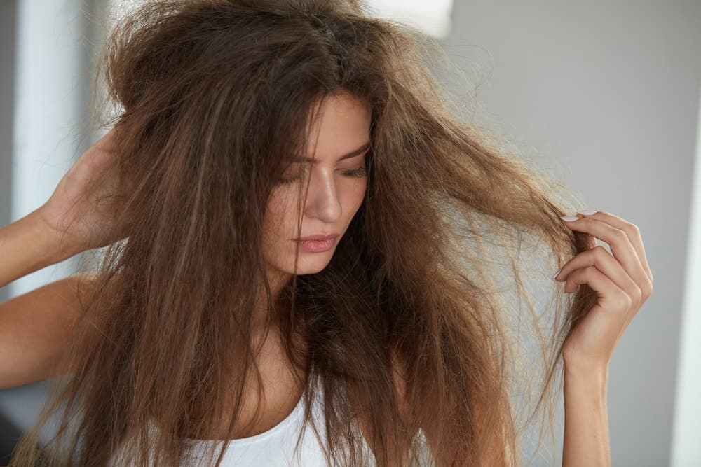 A woman with long, frizzy and damaged hair.