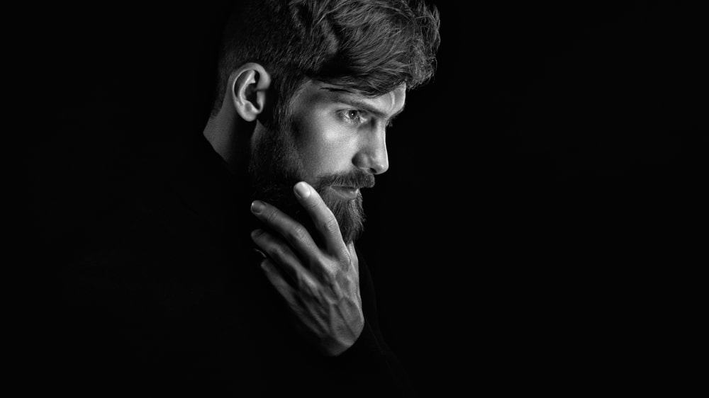 A man stroking his beard against a black background.
