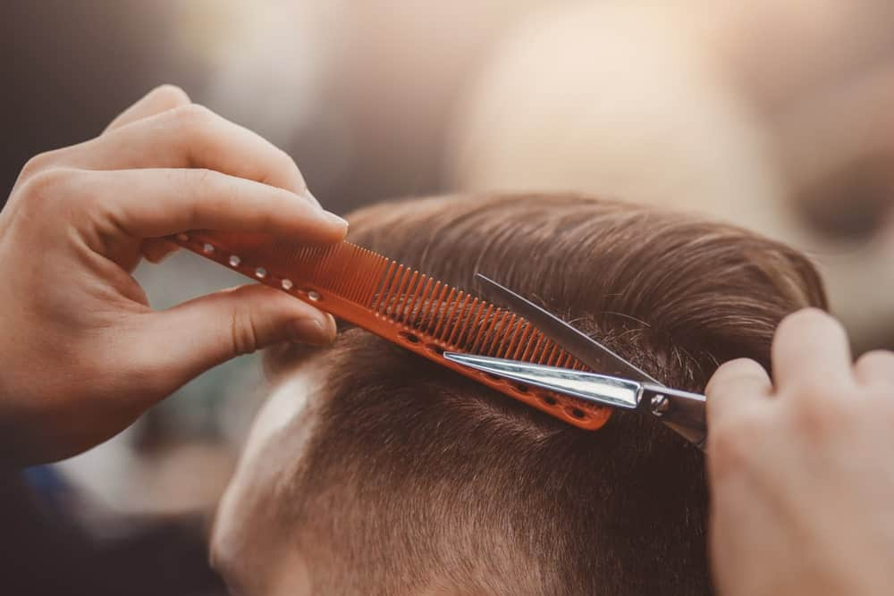 A close look at a barber comb being used in a barber shop.