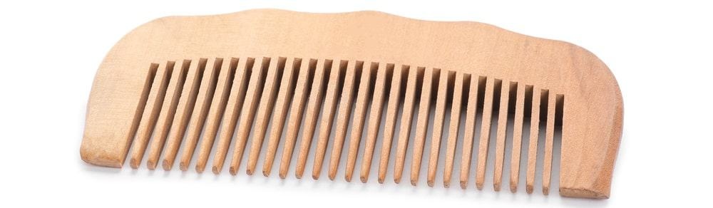 A close look at a wide-toothed wooden comb.