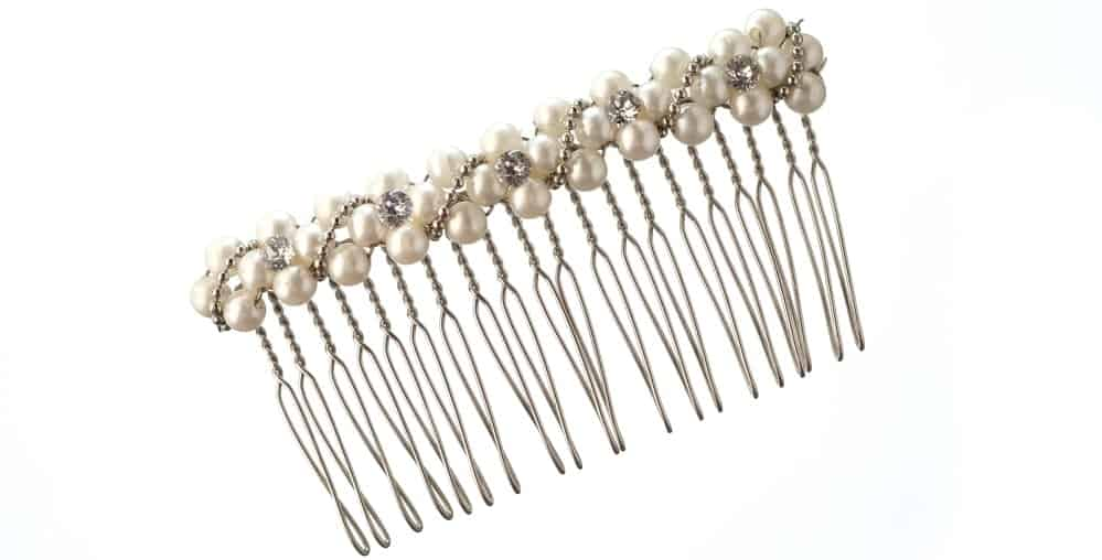 A close look at a side hair comb adorned with pearls.