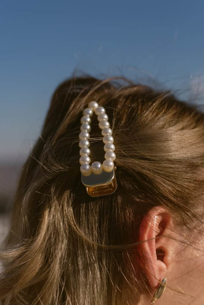 A woman wearing a barrette adorned with pearls.