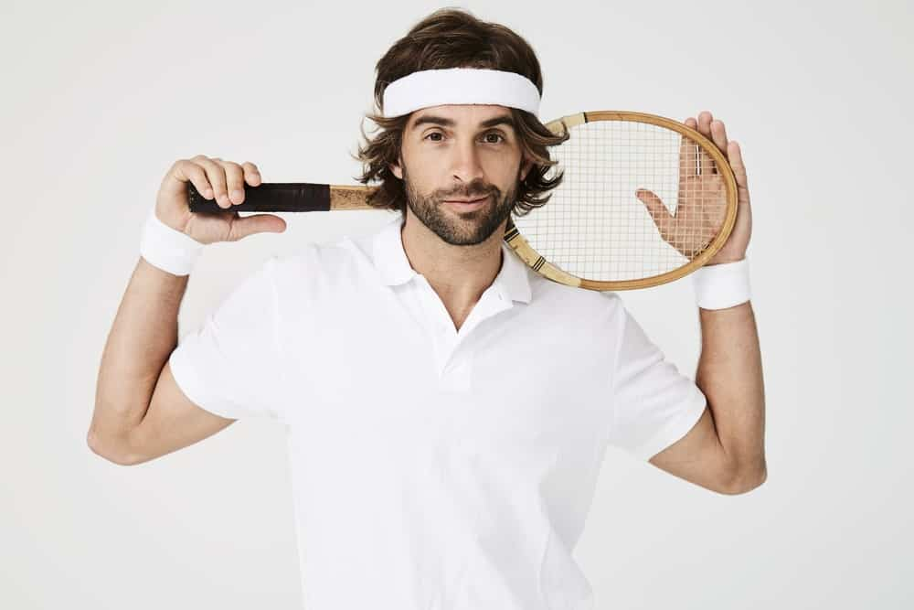A long-haired man wearing a white tennis headband.