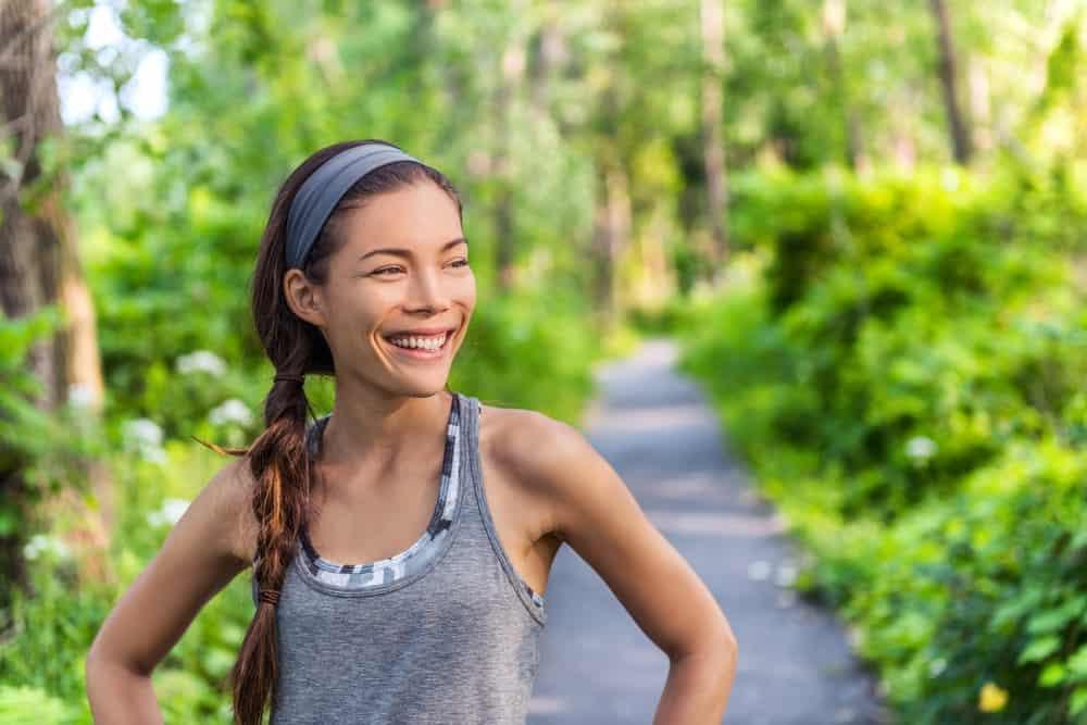 A woman wearing a gray sweatband at a jogging trail.