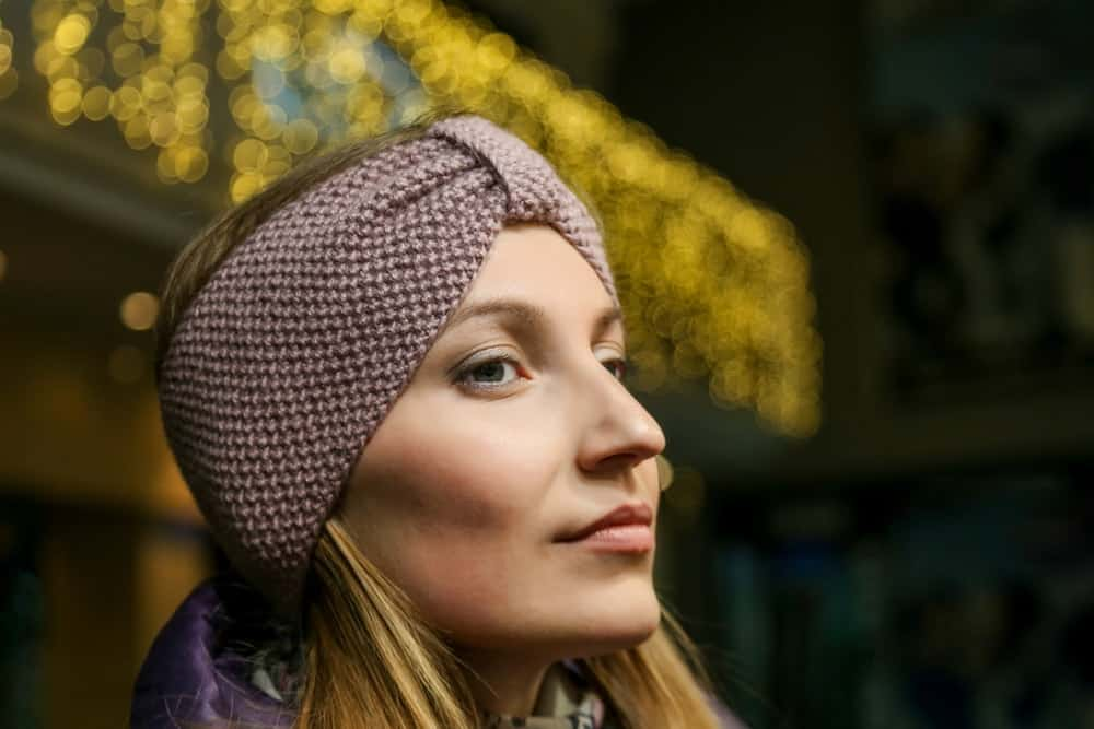 A close look at a woman wearing a brown knit headband.