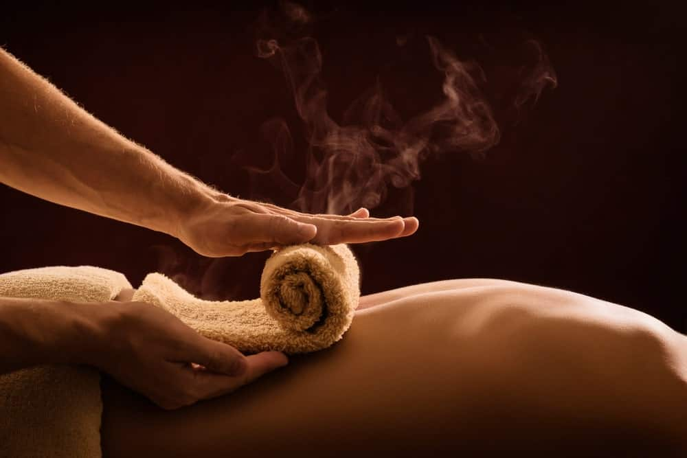 A massage therapist applying hot towel massage to the back of a man.