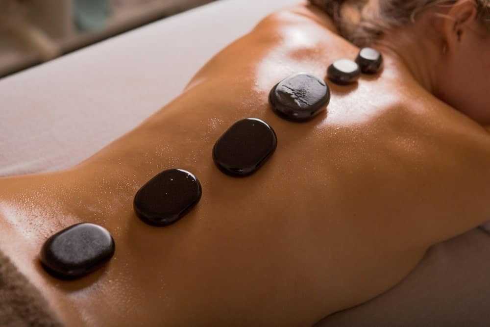A woman on a massage table having a hot stone massage.
