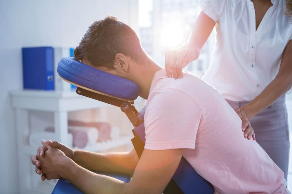 A physical therapist doing a medical massage on a man's back.