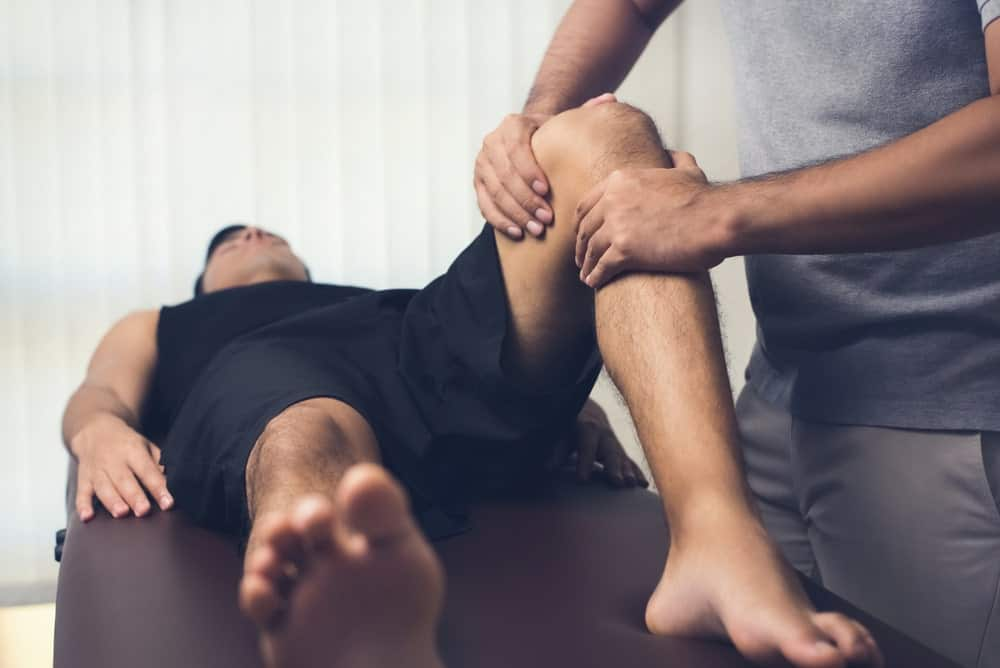 A sports therapist massaging the knee of an athlete.