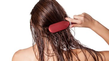 A woman brushing her long wet hair.