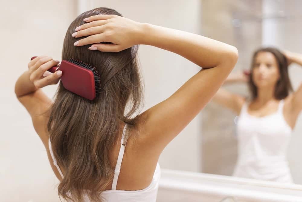A woman using a paddle hair brush on her long brown hair.