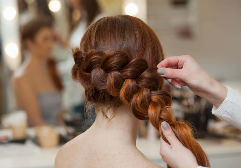 Back view of a woman with red hair being braided by a stylist.
