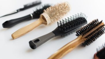 A variety of different brushes and combs on a white surface.