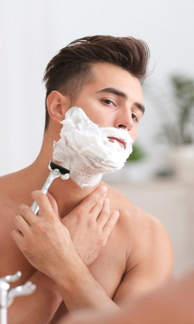 A close look at a man shaving in front of the bathroom mirror.