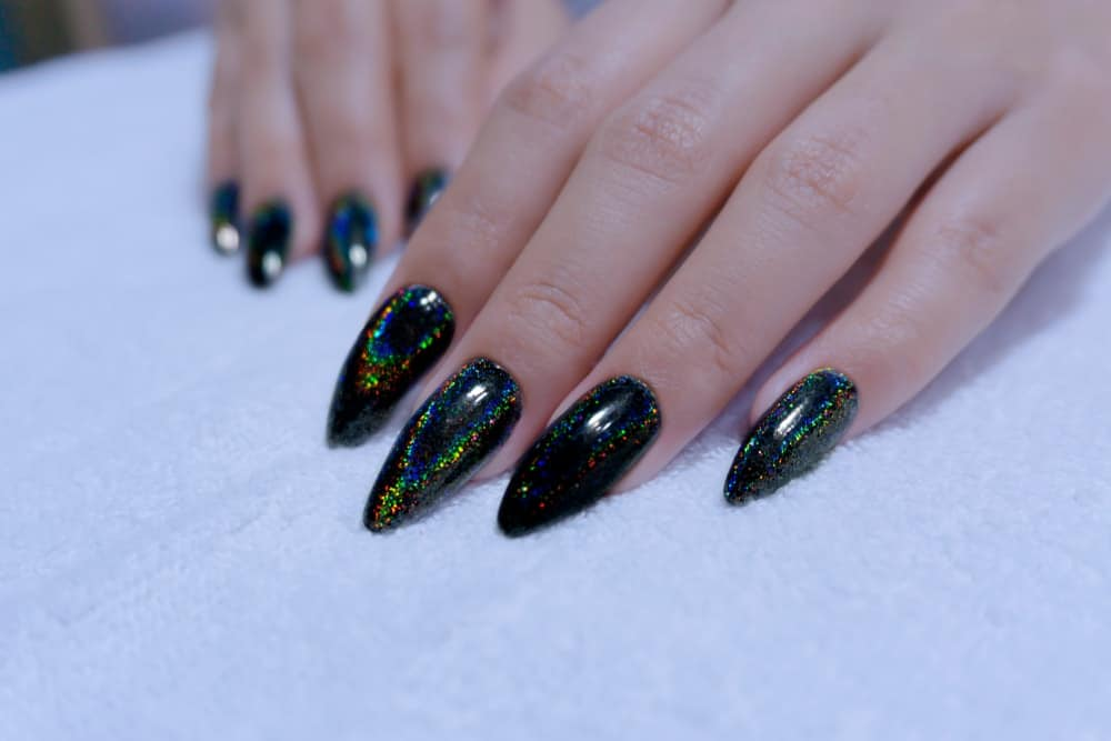 Closeup of fingernails painted in black gel hologram nail polish.