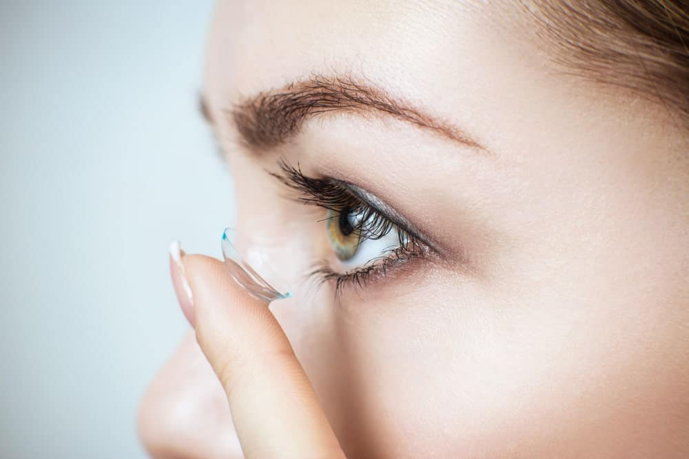 Woman putting clear contact lens in her left eye.
